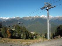 在山的空中览绳与绿色倾斜和多雪的山峰 免版税库存照片