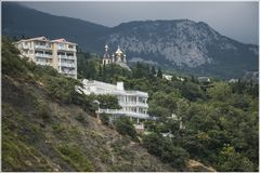 在山的绿色倾斜的雪白大厦 免版税库存图片