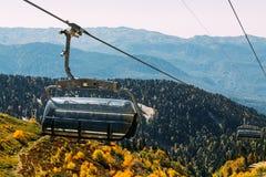 在山的缆索铁路的上流在秋天森林上 免版税库存图片