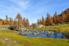 在山的美丽的小河与蓝天,红色树在秋天和老桥梁 库存照片