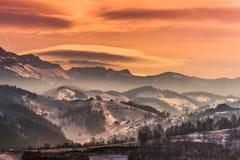 在山的美好的冬天在日落的风景与双突透镜的云彩和雪点燃 免版税库存图片