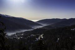 在山的美好的冬天日出临近城市 免版税库存图片