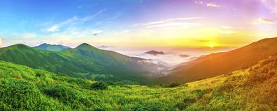在山的美好的日出与在全景下的白色雾 免版税图库摄影