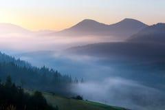 在山的美好的有雾的风景 发光由阳光的意想不到的早晨 免版税库存照片
