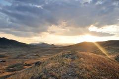 在山的美好的风景在日落 发光通过云彩的星期日光芒 库存图片