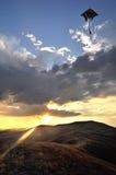 在山的美好的风景在日落 发光通过在天空的云彩风筝飞行的太阳光芒 免版税库存照片