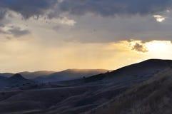 在山的美好的风景在日落 有雾的小山看法  飞行天空的鸟 库存照片