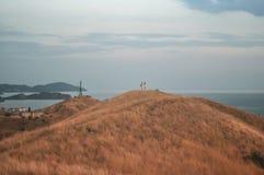 在山的美好的风景在日落 站立在小山的上面的人两个剪影与海的thr backgrou的 免版税库存照片