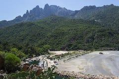 在山的脚与小船船坞和天蓝色海之间的白色海滩 库存图片