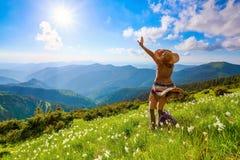 在山的草坪使礼服、长袜和草帽的行家女孩环境美化 免版税库存图片