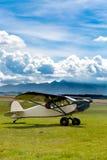 在山的草甸登陆的减速火箭的飞机 免版税库存图片