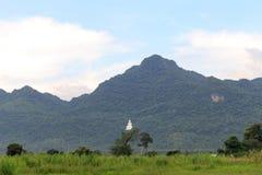 在山的菩萨雕象与多云 库存图片