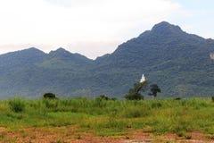 在山的菩萨雕象与多云 库存照片