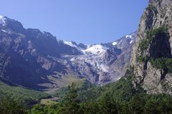 在山的谷,长满与木头和冰川在距离 库存图片