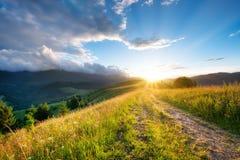 在山的路 草和日落 使自然夏天环境美化 太阳亮光和天空 农村的横向 免版税库存照片