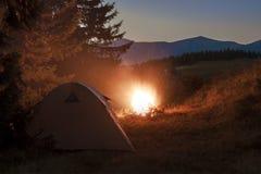 在山的远足者帐篷与篝火的晚上与闪闪发光 图库摄影