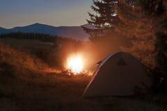 在山的远足者帐篷与篝火的晚上与闪闪发光 库存图片