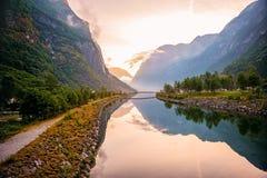 在山的金黄日出,与反射的Gudvangen挪威在海湾的水中 水平的框架 图库摄影