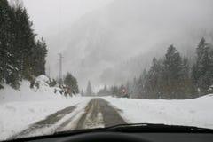 在山的雪风暴在汽车里面 库存照片