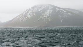 在山的风景看法与多雪的山峰和海水挥动 股票视频