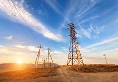 在山的高压塔在日落 电定向塔系统 免版税库存图片