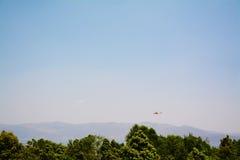 在山的直升机在清楚的天空的飞行和树 免版税库存照片