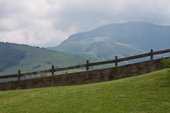 在山的绿色草甸牧场地背景与在多云天空的木篱芭 图库摄影