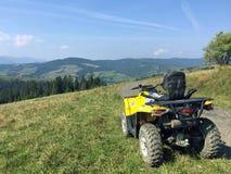 在山的黄色ATV 库存照片