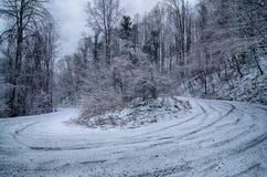 在山的S形曲线路在冬天雪风暴以后 免版税库存照片