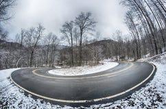 在山的S形曲线路在冬天雪风暴以后 库存图片