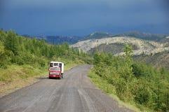 在山石渣路Kolyma高速公路的卡车在内地俄语 库存照片