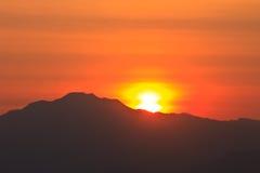 在山背景的日落 库存图片