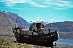 在山背景的老船  免版税库存图片