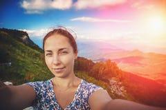 在山背景,夏天旅行的微笑的少妇作为selfie 库存图片