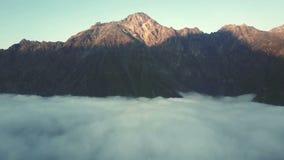 在山脉的空中寄生虫飞行通过在日落4K的云彩 股票录像