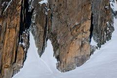 在山脉的Rockface在与登山人的冬天在墙壁上 库存图片