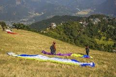 在山腰的滑翔伞在绿色山和房子背景准备离开  免版税图库摄影