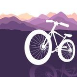 在山自然背景的自行车剪影 免版税库存图片