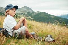 在山艰苦跋涉期间,年轻男孩采取休息在草甸 免版税库存图片