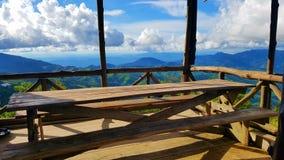 在山观点的木桌与蓝天和云彩 免版税库存照片