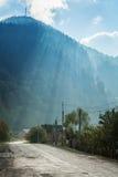 在山路的太阳光芒 免版税库存图片