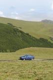 在山路的蓝色轿车汽车 库存照片