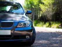 在山路的BMW 3系列E90 330i闪耀的石墨 免版税库存图片