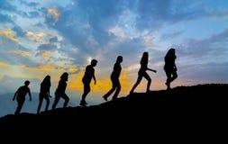 在山道路的七个朋友步行在日落 免版税库存照片