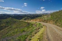 在山附近的乡下路 库存照片