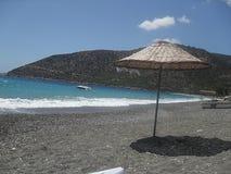 在山附近的沙滩伞 免版税库存照片