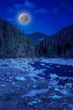 在山附近的河岩石岸在月光 库存照片