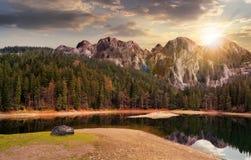 在山附近的湖在日落的杉木森林里 免版税库存图片