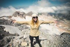 在山顶举的少妇愉快的手 免版税库存图片