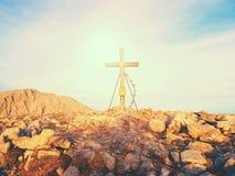 在山顶部的大十字架如典型在阿尔卑斯 与佛教祈祷的旗子的木十字架 免版税库存照片